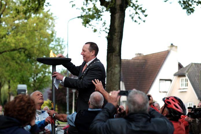 Rik de Lange, burgemeester van Duiven, ontsteekt de vlam bij het oorlogsmonument aan de Burg. Van Dorth tot Medlerstraat.  Archieffoto Jan van den Brink