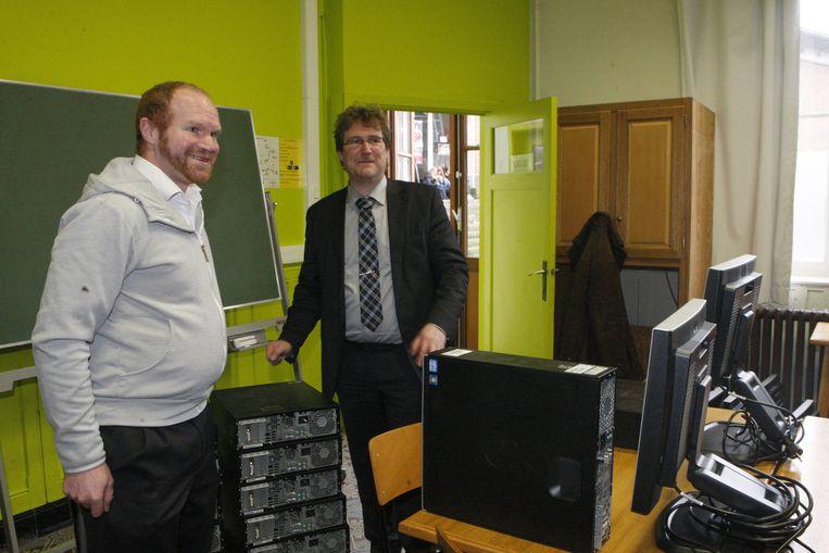 Dennis Gewillig (links ) schonk veertien computers aan het Via-college in Tienen. Directeur Geert Coenen nam ze in ontvangst.