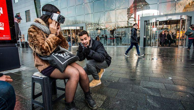 Voor De Markthal in Rotterdam doet een meisje mee aan een virtual reality-actie. Beeld Arie Kievit