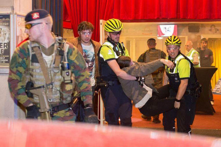 Een slachtoffer wordt uit de zaal gered terwijl een militair de wacht houdt.