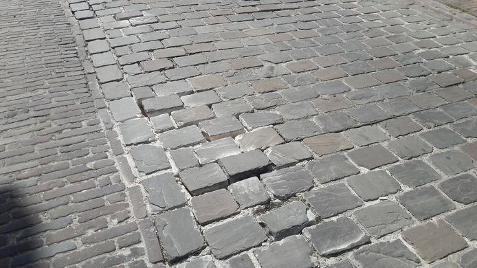Losgeraakte stenen klossen tegen elkaar aan als het verkeer door de Kerkstraat rijdt.