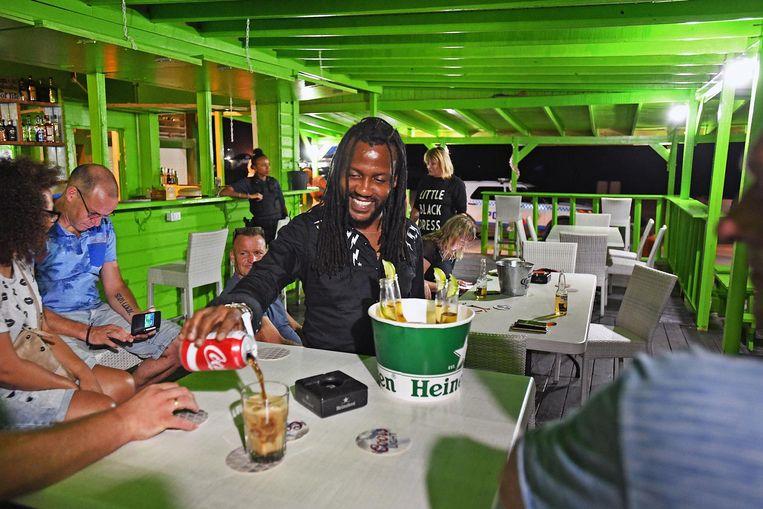 Tafari aan het werk in 'Oma's Kultuur Keuken'een klein restaurant aan de Boardwalk. Beeld Guus Dubbelman / de Volkskrant