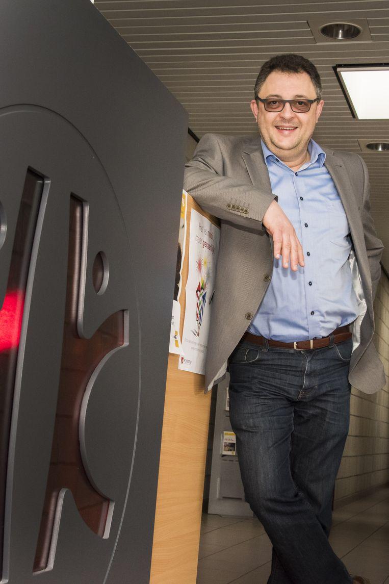 Patrick Vandijck bij het logo van Kortenaken in het gemeentehuis.