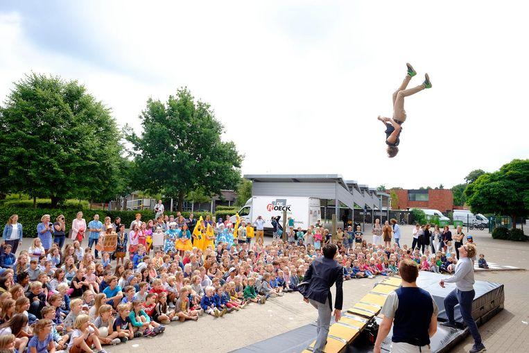 De leerlingen van de Albrecht Rodenbachschool kijken vol bewondering naar de spectaculaire circusact op de speelplaats.