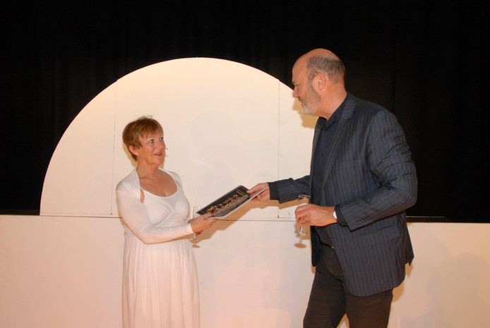 Theaterdirecteur Coen Bais overhandigde het eerste exemplaar van het jubileumboek van Internos aan Diny van Haandel, langst spelend lid van de vereniging.