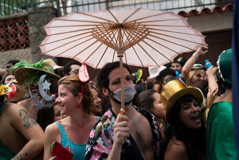 Een Braziliaan met mondmasker bij een straatfeest in het Braziliaanse Rio de Janeiro. Beeld AP