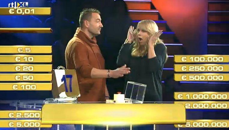 Van den Hurk (l) vlak voordat hij op de rode knop drukt in de spelshow Miljoenenjacht. Presentatrice Linda de Mol reageert met veel gevoel voor drama. Beeld