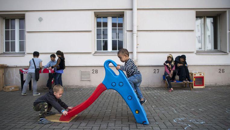 Kinderen spelen in het voormalige gemeentehuis van de Berlijnse wijk Wilmersdorf, dat nu als asielzoekerscentrum dient. Beeld afp