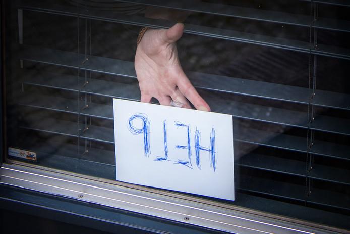 Het briefje dat het ouder echtpaar voor het raam hield nadat ze door overvallers in eigen huis bedreigd, opgesloten en bestolen waren.