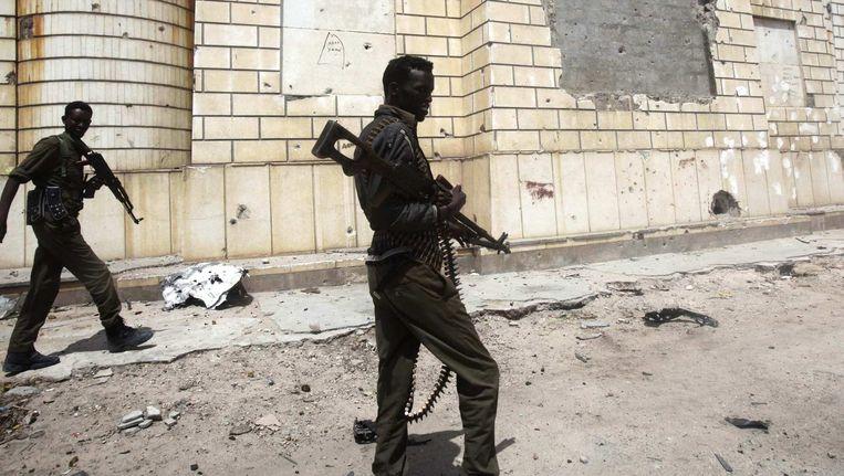 Somalische soldaten patrouilleren de straten van Mogadishu nabij de plek waar een zelfmoordaanslag is gepleegd met een auto. Beeld reuters