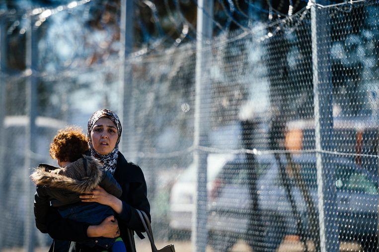 Een migrant met haar kind bij de grens tussen Griekenland en Noord-Macedonië, 2016. Beeld AFP