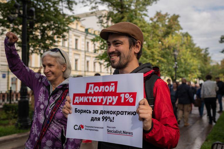 Roman met een bord waarop staat: 'Klaar met dictatorschap van 1 procent. Vecht voor democratie voor 99 procent' Beeld Yuri Kozyrev