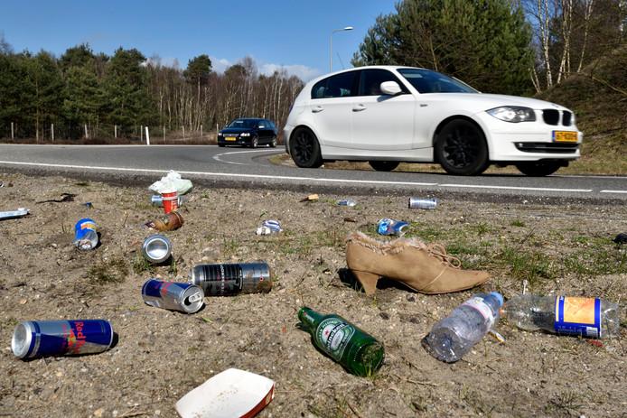 Volop blikjes en ander afval in de berm langs een weg.
