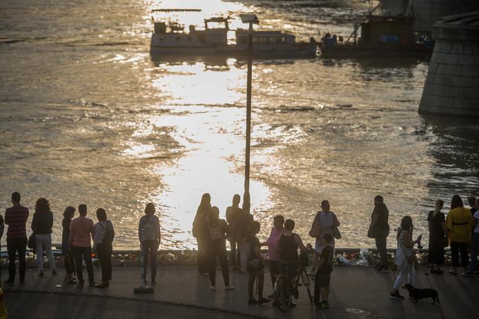 Mensen staan stil bij de gekapseisde rondvaartboot met Zuid-Koreaanse toeristen.