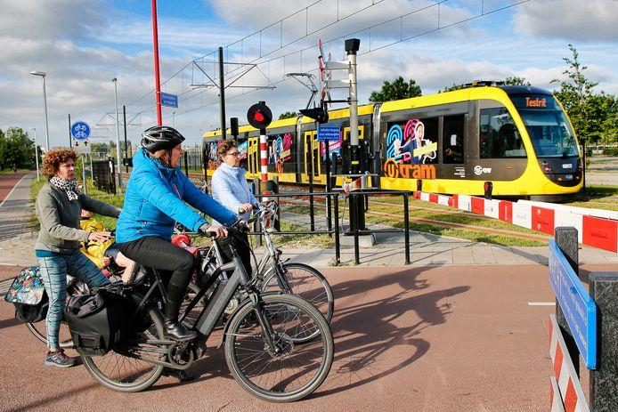 Fietsers wachten bij spoorbomen op de Koningsweg terwijl de testrit van de Uithoflijn langsrijdt