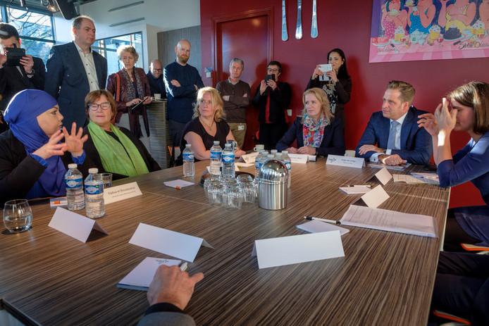 Hugo de Jonge in discussie met Schiedamse zorgverleners. Links van hem luistert wethouder Patricia van Aaken mee.