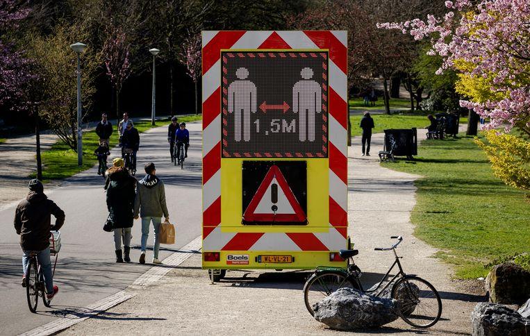 Een bord waarschuwt in het Vondelpark om 1,5 meter afstand te houden van elkaar. Beeld ANP