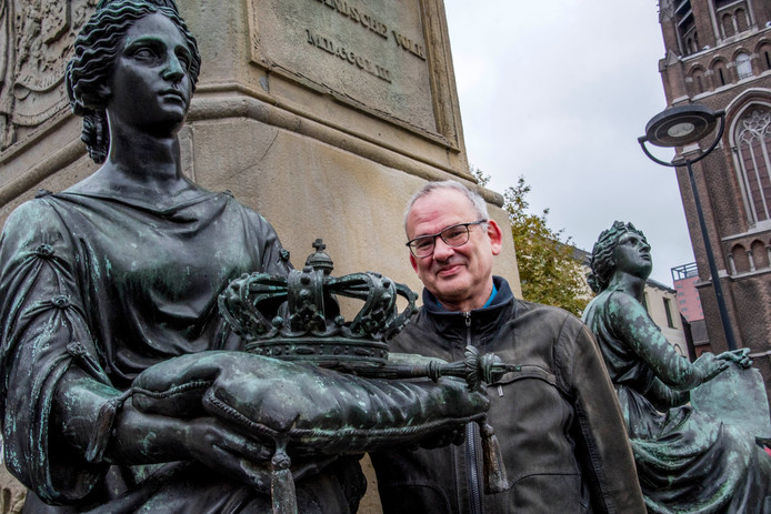 Luc Brants tussen de allegorische dames van het standbeeld van koning Willem II, over wiens homoseksuele avonturen in het Tilburg van de negentiende eeuw niet gepraat werd.
