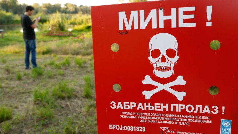 Een man in Bosnië speelt Pokémon Go in de plaats Brcko, naast een bord waarop wordt gewaarschuwd voor mijnen.
