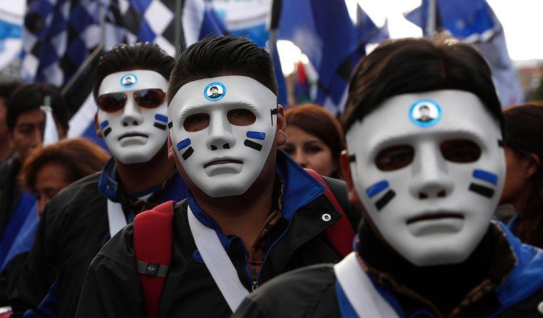 Sommige aanhangers van president Evo Morales dragen een masker als steunbetuiging. Beeld AP