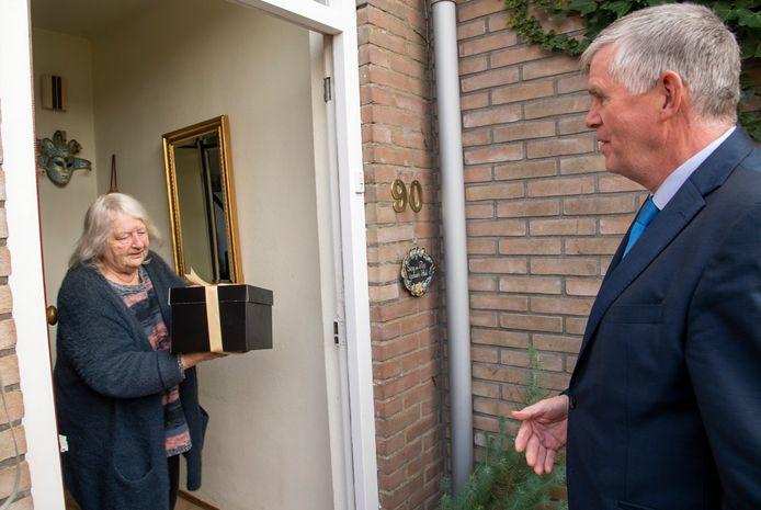 Burgemeester André Baars van Ermelo overhandigt een maaltijd aan Sieny IJzebaart.