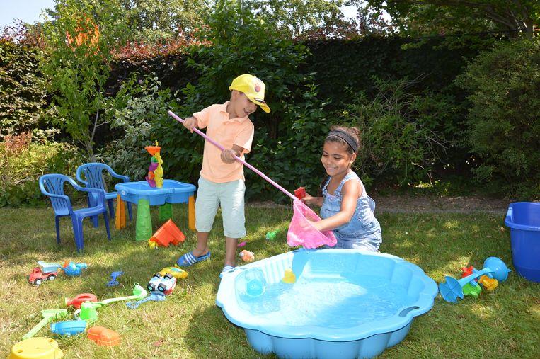 Yasmine en Ismaël spelen met eendjes in het water in de tuin van Speelodroom.
