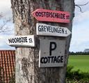 Richtingwijzers bij de parkeerplaats van vakantiewoning The Cottage van Rob van der Pauw.
