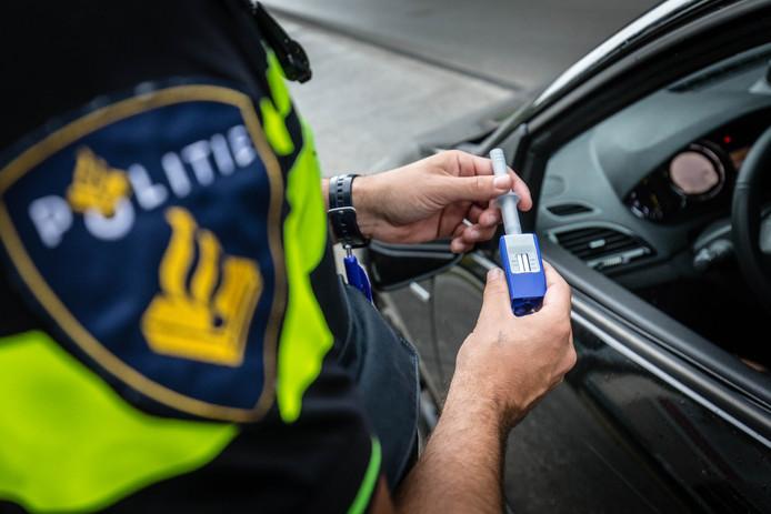 Een agent neemt tijdens een verkeerscontrole een speekseltest af. Foto ter illustratie.
