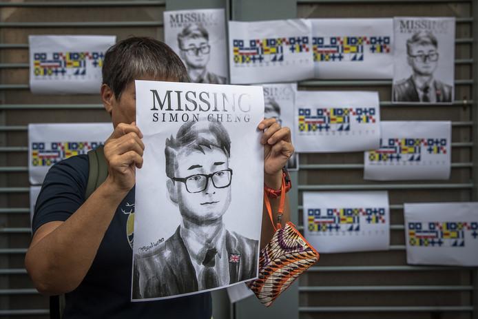 Een betoger met een plakkaat met de foto van de inmiddels vrijgelaten Brit Simon Cheng.