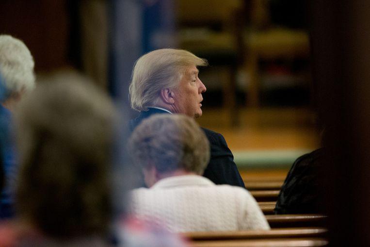 Trump op de vijfde rij van de kerkbanken. Beeld null