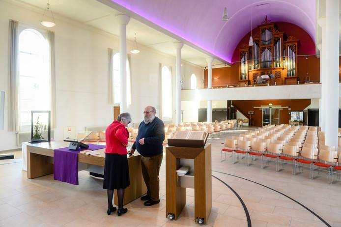 Voorganger Lieke Sies checkt haar microfoon en controleert wat laatste details met kerkenraadsvoorzitter Roelof Reinders, terwijl Ab Heuvelink achter het klavier van het orgel zit.