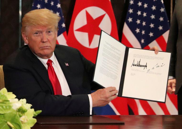 Trump toont trots het ondertekende document.