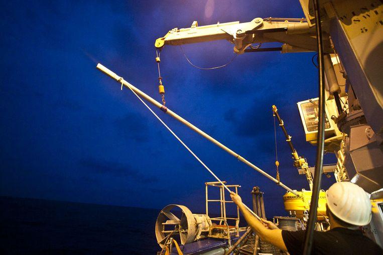 De piston core is net terug van zijn reis naar de diepzee, en levert een flinke cilinder af. Beeld Ronald Veldhuizen