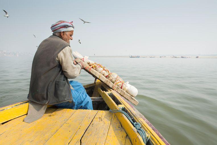 Een grootvader laat zijn overleden kleinkind - vastgebonden aan een steen - in het water van de Ganges zakken. Kinderen onder de tien jaar en zwangere vrouwen zijn zuiver en hoeven daarom niet verbrand te worden. Beeld Lieve Blancquaert