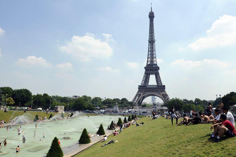 Mensen nemen woensdag bij de Eiffeltoren in Parijs een verfrissende duik. De temperaturen stegen tot boven de 30 graden in de Franse hoofdstad. (AFP) Beeld