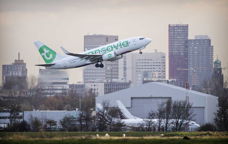 Een vliegtuig van Transavia stijgt op vanaf vliegveld Rotterdam The Hague Airport, met op de achtergrond de hoogbouw van de stad Rotterdam.
