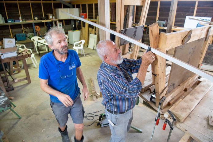 Scheepsbouwmeester Harmen Timmerman (links) en Gerrit Veerman zijn druk in de loods bezig met de bouw van de zomp.