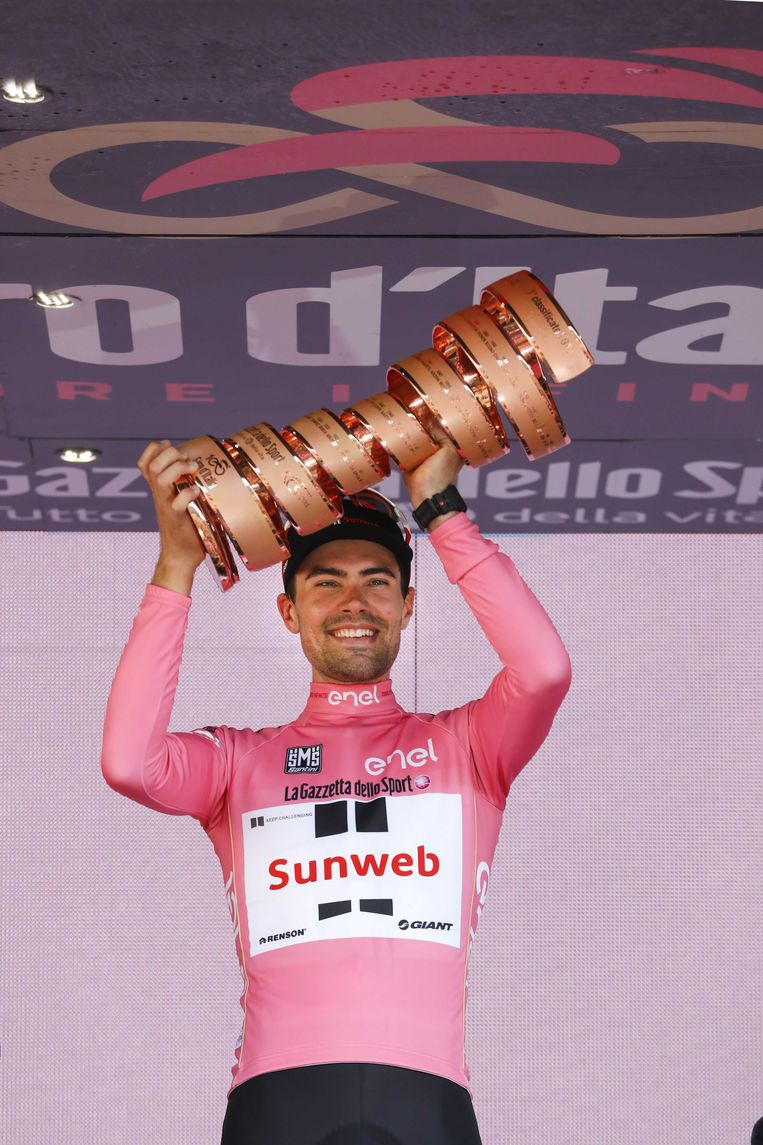 Dumoulin in roze leiderstrui en met trofee op het erepodium na het winnen van de Giro d'Italia in 2018.  Beeld ANP
