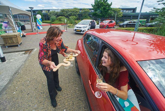 Drive in diplomauitreiking ROC De Leijgraaf Veghel. Isa van Roosmalen neemt nadat ze haar diploma heeft gekregen champagne aan neemt van docente Jeanne Schimmel. En na haar volgden er nog velen.