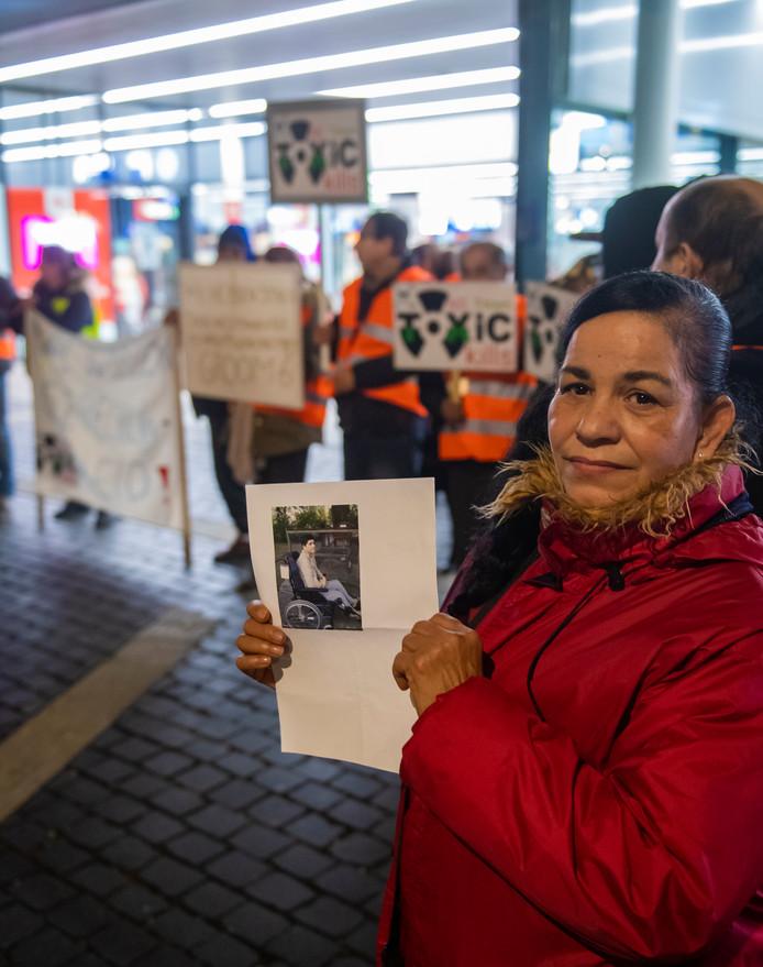 Tilburg Xiomara Maal was een van de deelnemers vrijdag tijdens een chroom-6 protest op station Tilburg. Ze toont een foto van haar aan kanker overleden broer Carlos die ook deelnam aan het treinenproject.