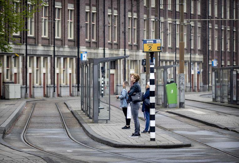 Een plukje passagiers wacht op de tram bij Amsterdam Centraal.  Beeld Koen van Weel / EPA