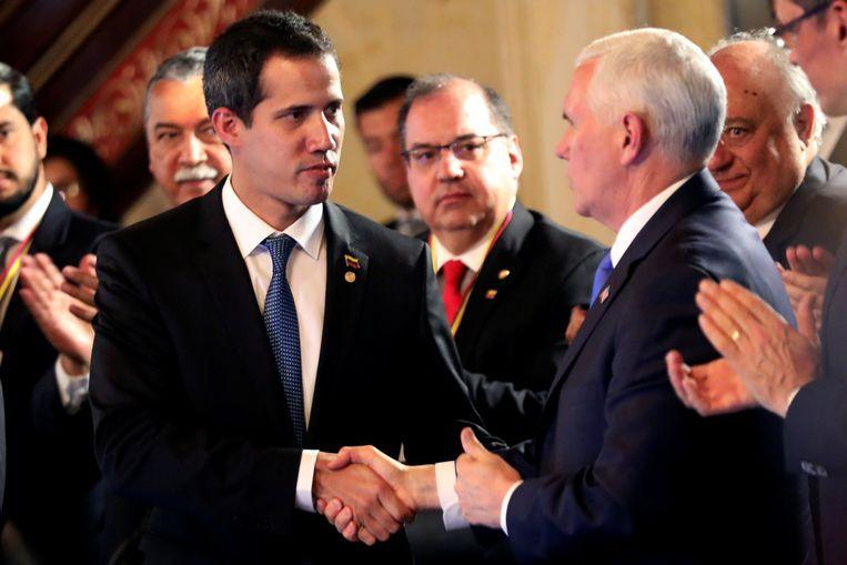 Juan Guaido schudt de hand van Mike Pence bij de bijeenkomst van de Limagroep. Beeld Reuters
