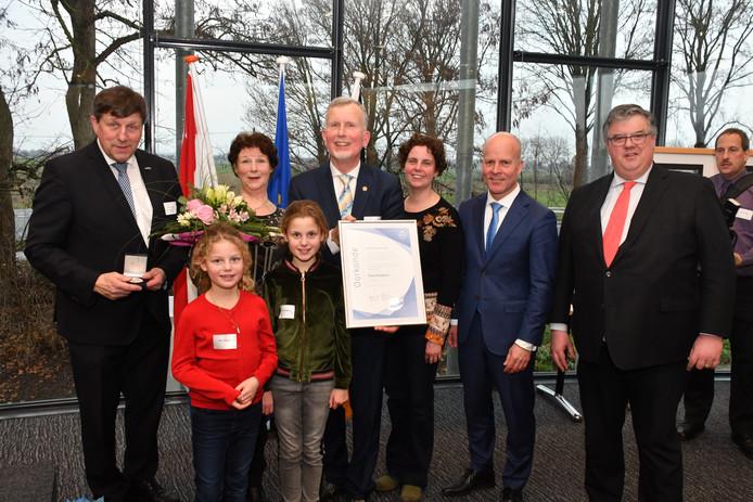Theo Giesbers kreeg, omringd door familie, staatssecretaris Raymond Knops (blauw pak) en de burgemeesters Francken (l) en Bruls, de erepenning van de Euregio Rijn-Waal.  Foto Henk Baron