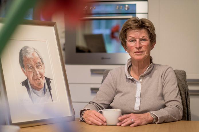 Sini Wijnen met portret van Dik Wessels, met wie ze bijna 43 jaar samenwerkte.