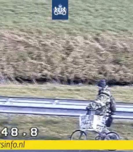 Man in camouflagekleding wandelt met een fiets aan de hand langs de snelweg