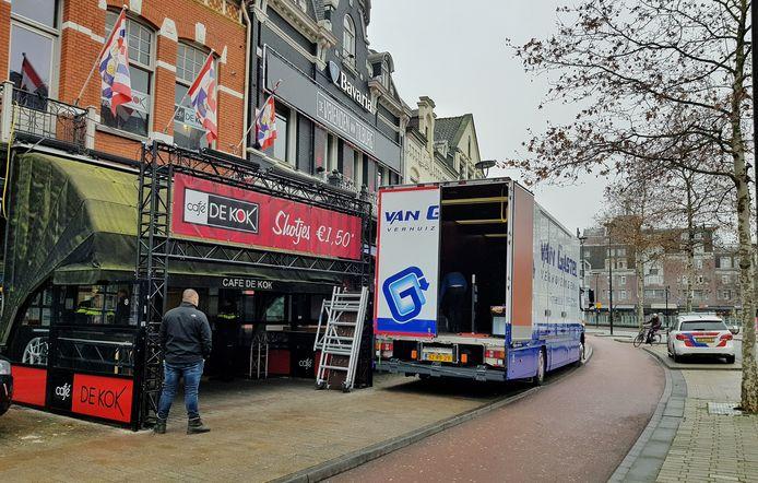 Verhuizers halen het meubilair uit café De Kok en zetten het in een vrachtwagen.