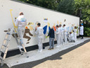 Een ploeg van schildersbedrijf Somers kleurt de tekening van Luc Verschuuren op de Somerse Dag van 2019 in