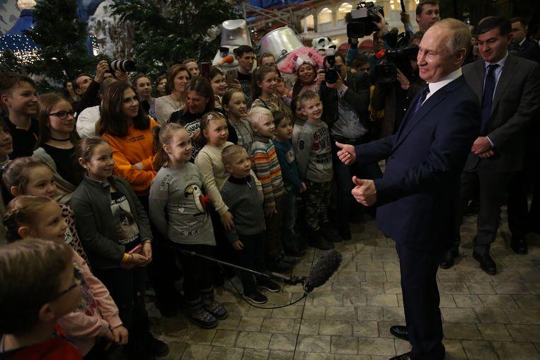 Vladimir Poetin spreekt kinderen toe tijdens een bezoek aan een pretpark. Beeld Getty Images