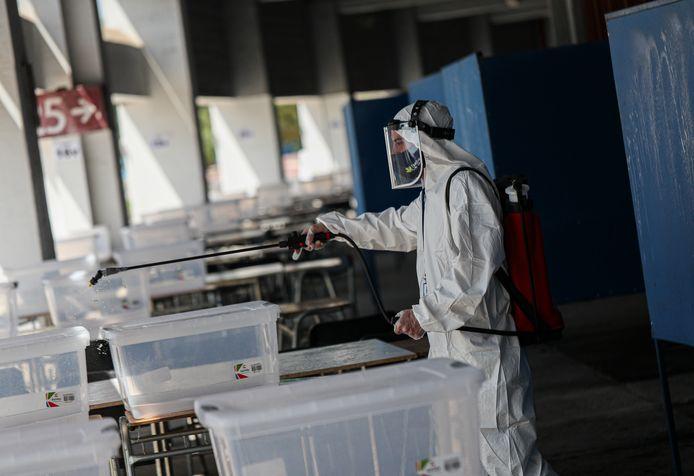 Een arbeider desinfecteert een stembureau in hoofdstad Santiago.