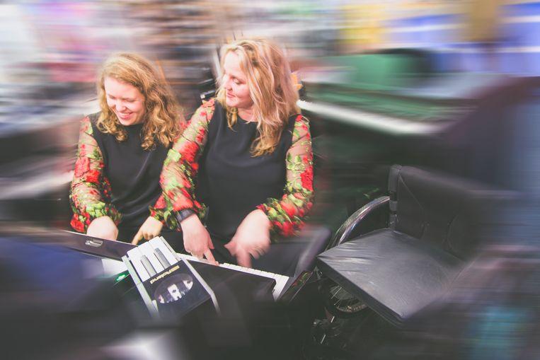 Lien uit Gent (links) leeft zich samen met een ander model uit op een piano. Je moet al goed kijken om haar armprothese te kunnen opmerken.